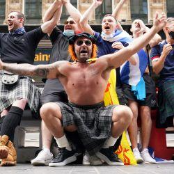 Los aficionados escoceses animan en la estación central de Glasgow mientras se preparan para viajar a Londres antes del partido del Grupo D de la Eurocopa 2020 entre Inglaterra y Escocia en el estadio de Wembley. | Foto:Jane Barlow / PA Wire / DPA