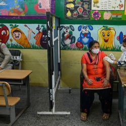 Un trabajador sanitario inocula a una mujer una dosis de la vacuna Covishield contra el coronavirus Covid-19 en una escuela utilizada temporalmente como centro de vacunación en Nueva Dehi.   Foto:Prakash Singh / AFP
