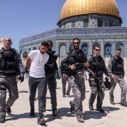 Miembros de la seguridad israelí llevan detenido un hombre palestino frente a la mezquita de la Cúpula de la Roca en Jerusalén, durante una protesta de los palestinos en respuesta a los cánticos de los ultranacionalistas israelíes dirigidos al profeta Mahoma en la Marcha de las Banderas.   Foto:Ahmad Gharabli / AFP