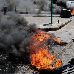 Manifestantes libaneses bloquean las calles de Beirut con neumáticos ardiendo para protestar contra el deterioro de la situación económica del país. | Foto:Joseph Eid / AFP