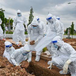 Voluntarios con trajes de protección entierran el cuerpo de una víctima del coronavirus Covid-19 en el cementerio musulmán Raudhatul Sakinah en Kuala Lumpur. | Foto:Mohd Rasfan / AFP