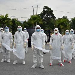 Voluntarios con trajes de protección posan para una foto antes de enterrar el cuerpo de una víctima del coronavirus Covid-19 en el cementerio musulmán Raudhatul Sakinah en Kuala Lumpur.   Foto:Mohd Rasfan / AFP