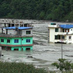 Esta vista general muestra casas sumergidas en las aguas de las inundaciones en Sindhupalchok, a unos 70 km al noreste de Katmandú, después de que las fuertes lluvias monzónicas provocaran el desbordamiento del río Melamchi. | Foto:Prakash Mathema / AFP