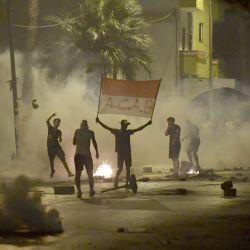 Las fuerzas de seguridad tunecinas disparan gas lacrimógeno mientras los manifestantes que sostienen una pancarta con la leyenda  | Foto:Fethi Belaid / AFP