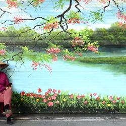 Una mujer se sienta frente a una tienda cerrada en Hanoi.   Foto:Manan Vatsyayana / AFP