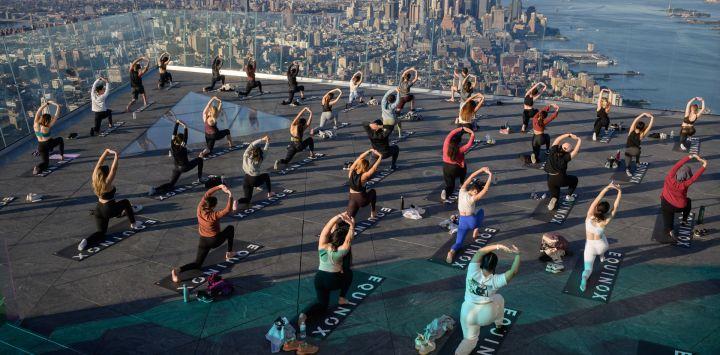 Practicantes de yoga asisten a una clase en el Edge Observation Deck, anunciado como la