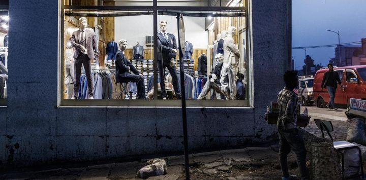 Un hombre sostiene una cesta con mercancía a la venta en una esquina de una calle de la zona de Piazza de Addis Abeba, mientras un perro callejero duerme en la vereda.