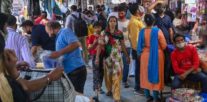 La gente compra en un mercado abarrotado después de que las autoridades suavizaran el cierre impuesto como medida preventiva contra el coronavirus Covid-19, en Nueva Delhi.