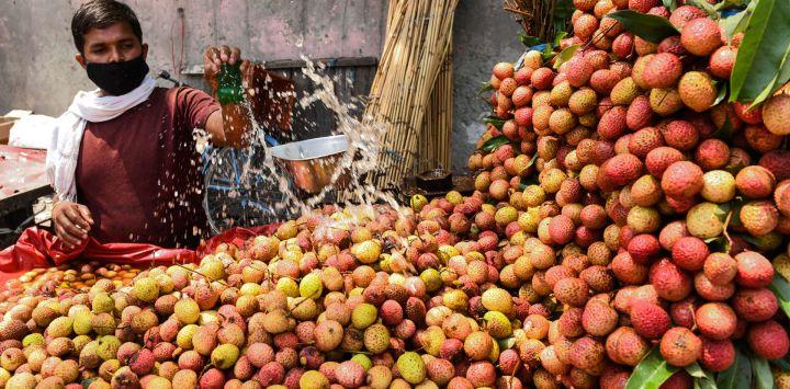 Un vendedor salpica agua sobre los lichis mientras espera a los clientes en Amritsa.