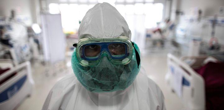 Un personal médico mira a la cámara mientras revisa a los pacientes del COVID-19 en la sala de la unidad de cuidados intensivos del Hospital General Regional de la ciudad de Bogor.