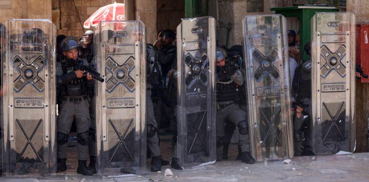Miembros de las fuerzas de seguridad israelíes permanecen en alerta durante una protesta de los palestinos en respuesta a los cánticos de los ultranacionalistas israelíes dirigidos al profeta Mahoma en la Marcha de las Banderas.