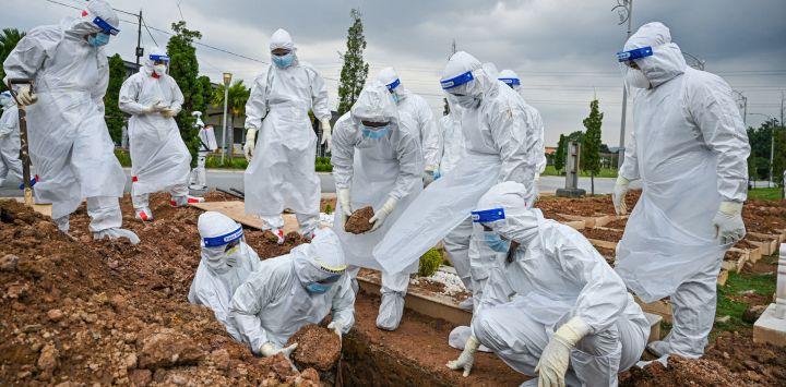Voluntarios con trajes de protección entierran el cuerpo de una víctima del coronavirus Covid-19 en el cementerio musulmán Raudhatul Sakinah en Kuala Lumpur.
