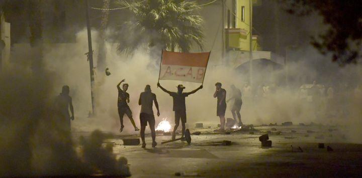 Las fuerzas de seguridad tunecinas disparan gas lacrimógeno mientras los manifestantes que sostienen una pancarta con la leyenda