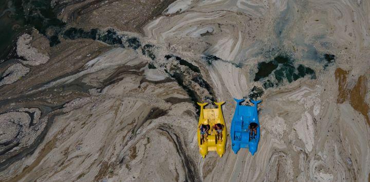 Esta fotografía aérea tomada en el distrito de Darica, en Kocaeli (Turquía), muestra a unos botes que navegan por el mar de Mármara cubiertos de moco de mar, una capa gelatinosa de baba que se desarrolla en la superficie del agua debido a la excesiva proliferación de fitoplancton, lo que supone una grave amenaza para el bioma marino.