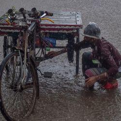 Un hombre con una bolsa de polietileno en la cabeza revisa su carro de bici-rickshaw mientras llueve en Dhaka. | Foto:Munir Uz Zaman / AFP