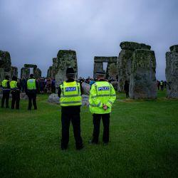 La policía observa cómo la multitud celebra el solsticio de verano dentro del círculo de piedra de Stonehenge. La gente saltó la valla para entrar en el lugar y ver el amanecer del día más largo del Reino Unido. | Foto:Ben Birchall / PA Wire / DPA