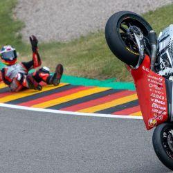 El piloto italiano Simone Corsi yace en el suelo tras su caída durante el Gran Premio de Alemania de MotoGP, Moto2, en el circuito de Sachsenring. | Foto:Jens Büttner / dpa-Zentralbild / DPA