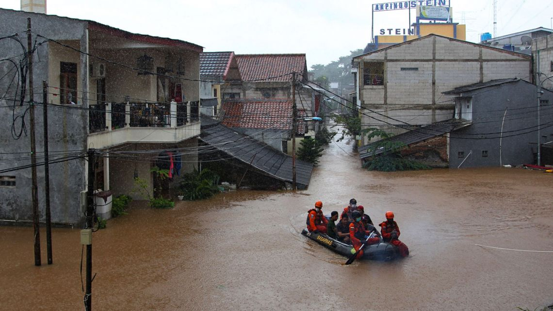 In this file photo taken on February 20, 2021, rescue personnel paddle a raft through a flood-affected neighbourhood in Jakarta following heavy overnight rains.