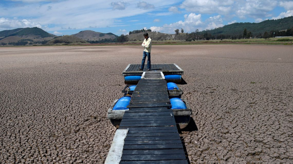 In this file photo taken on March 9, 2021, Colombian engineer and resident Hernan Sandino, stands next to the Suesca lagoon which has dried up due to a strong drought produced by climate change since 2012, according to environmental authorities, in Cucunaba municipality, Cundinamarca deparment, Colombia.