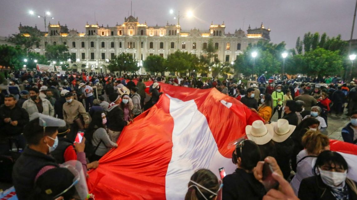 Supporters of leftist presidential candidate Pedro Castillo of Peru Libre display a giant national flag during a rally in downtown Lima on June 12, 2021.
