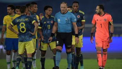Néstor Pitana, rodeado de jugadores colombianos tras el primer gol de Brasil. // NA