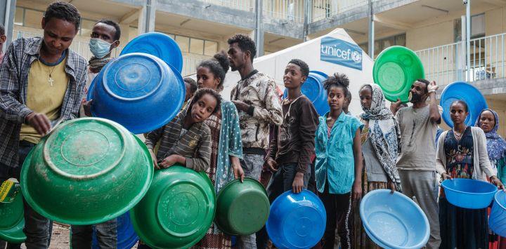 Las personas que huyeron de la violencia en la región etíope de Tigray esperan a recibir injeras, el alimento básico etíope de pan plano fermentado agrio, en su cocina como única comida del día en la escuela secundaria May Weyni, que ahora acoge a 1.500 desplazados como campo de desplazados internos, en Mekele, la capital de la región de Tigray.