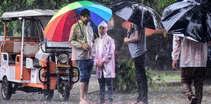 La gente sostiene paraguas durante una fuerte lluvia en Allahabad.
