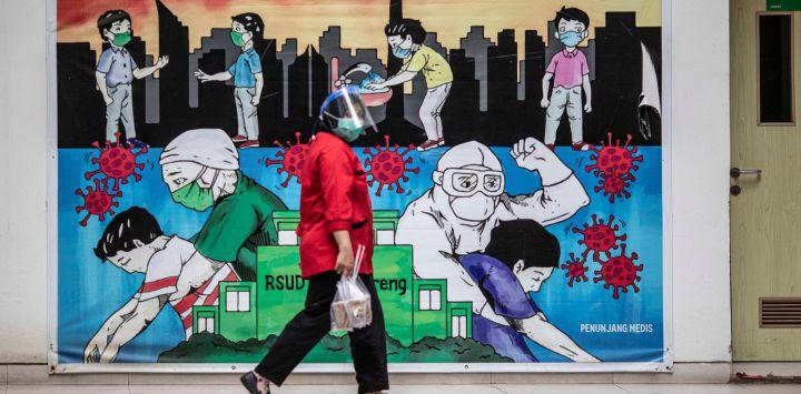 Una mujer pasa junto a un mural de covid-19 en el Hospital General Regional de Cengkareng. Indonesia ha experimentado un aumento significativo de los casos de emergencia de COVID-19.