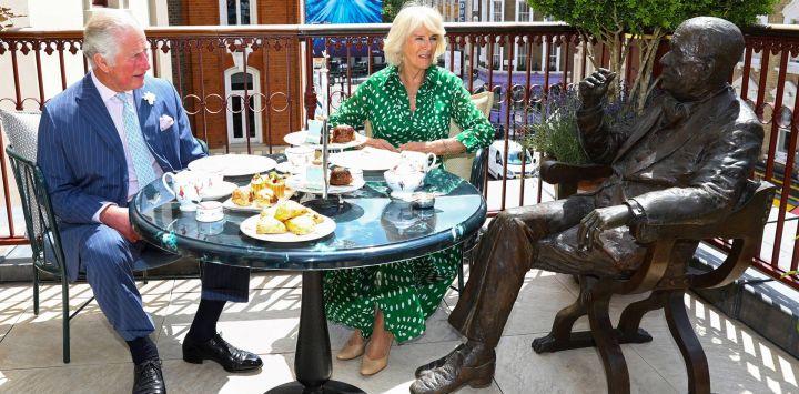 El Príncipe Carlos de Inglaterra, Príncipe de Gales, y Camilla, Duquesa de Cornualles, toman el té en la terraza junto a una estatua de tamaño natural del dramaturgo británico Noel Coward mientras visitan el Theatre Royal Drury Lane tras su remodelación en Londres.