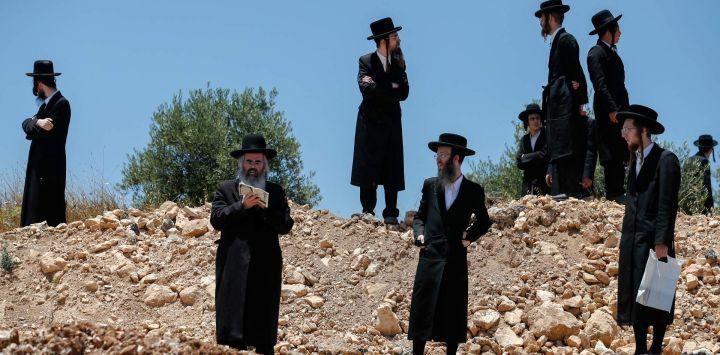 Hombres judíos ultraortodoxos se reúnen durante una manifestación contra la ampliación de una carretera en un lugar que se cree que alberga antiguas tumbas judías, cerca del asentamiento israelí de Elaza,r al sur de Belén en la Cisjordania ocupada.