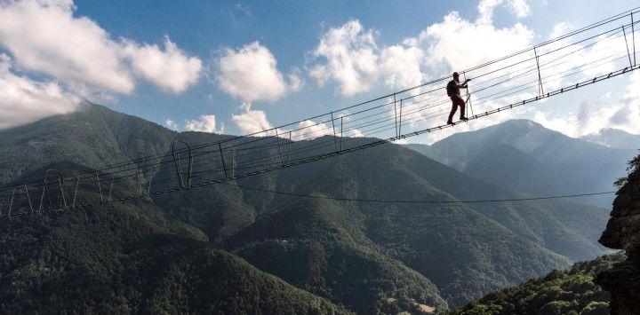 Un alpinista camina por un puente tibetano en el valle de Varaita, cerca de Busca, en el noroeste de Italia.