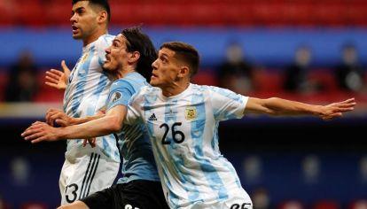 SEGURIDAD. Cristian Romero y Nahuel Molina le aportan seguridad y solvencia a la defensa de Argentina. Aquí, anulando a Edison Cavani.