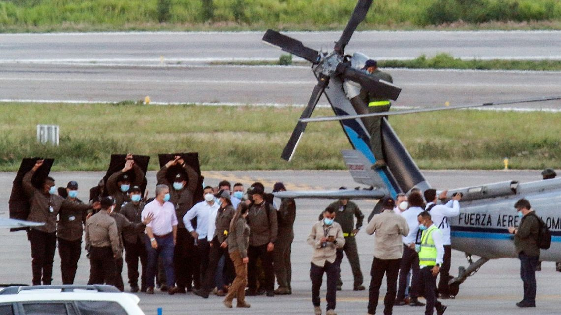 Colombia's President Iván Duque walks surrounded by bodyguards close to the presidential helicopter at the tarmac of the Camilo Daza International Airport after it was hit by gunfire in Cucuta, Colombia on June 25, 2021.