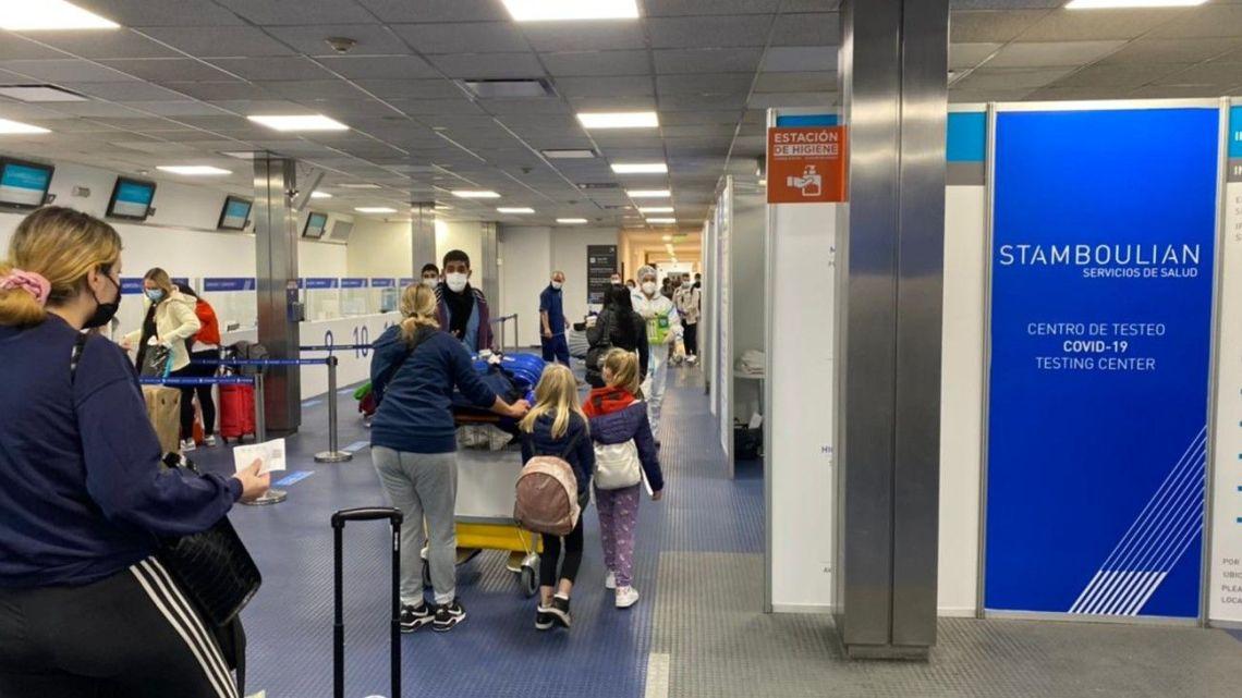 Passengers wait to be tested for coronavirus at Ezeiza international airport.