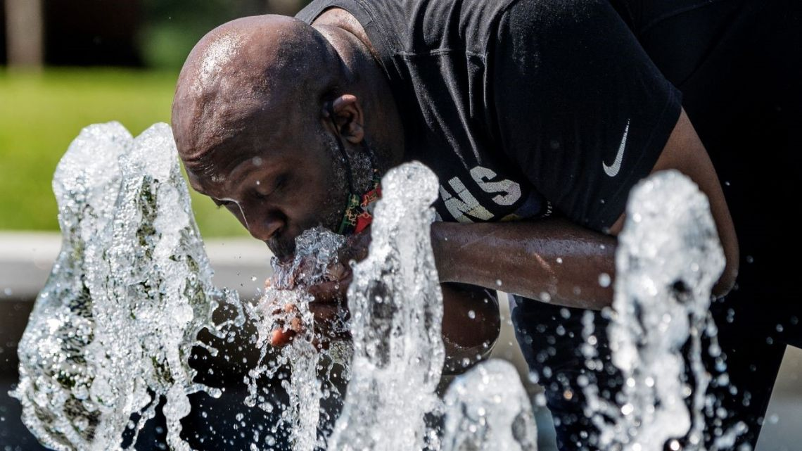A man drinks from a fountain at Inner Harbor in Baltimore, Maryland, on June 30, 2021, as a heat wave threatens to make it Baltimore's hottest day of the year.