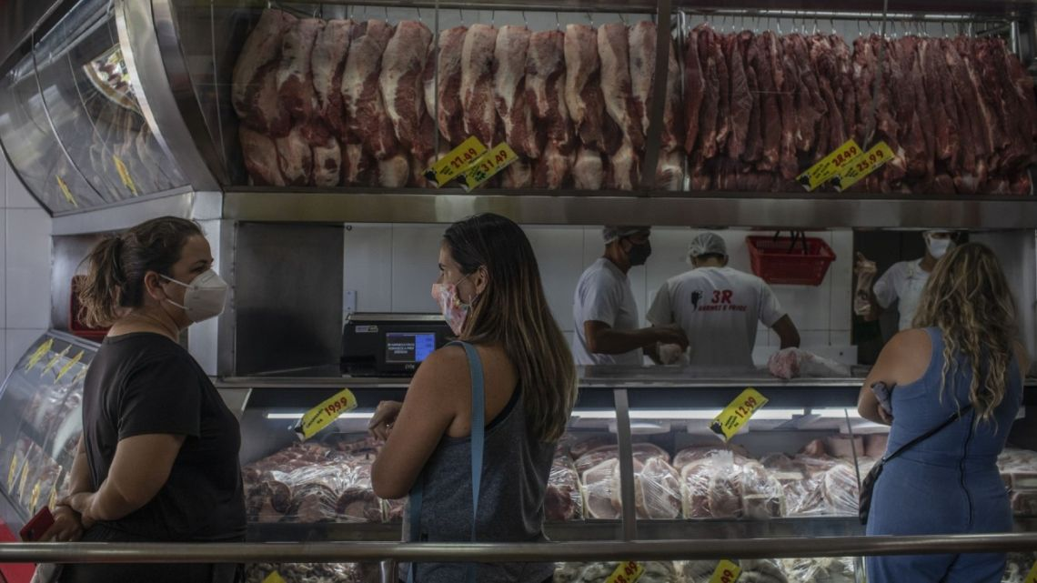 Customers shop for meat at a grocery store in Brasilia, Brazil.