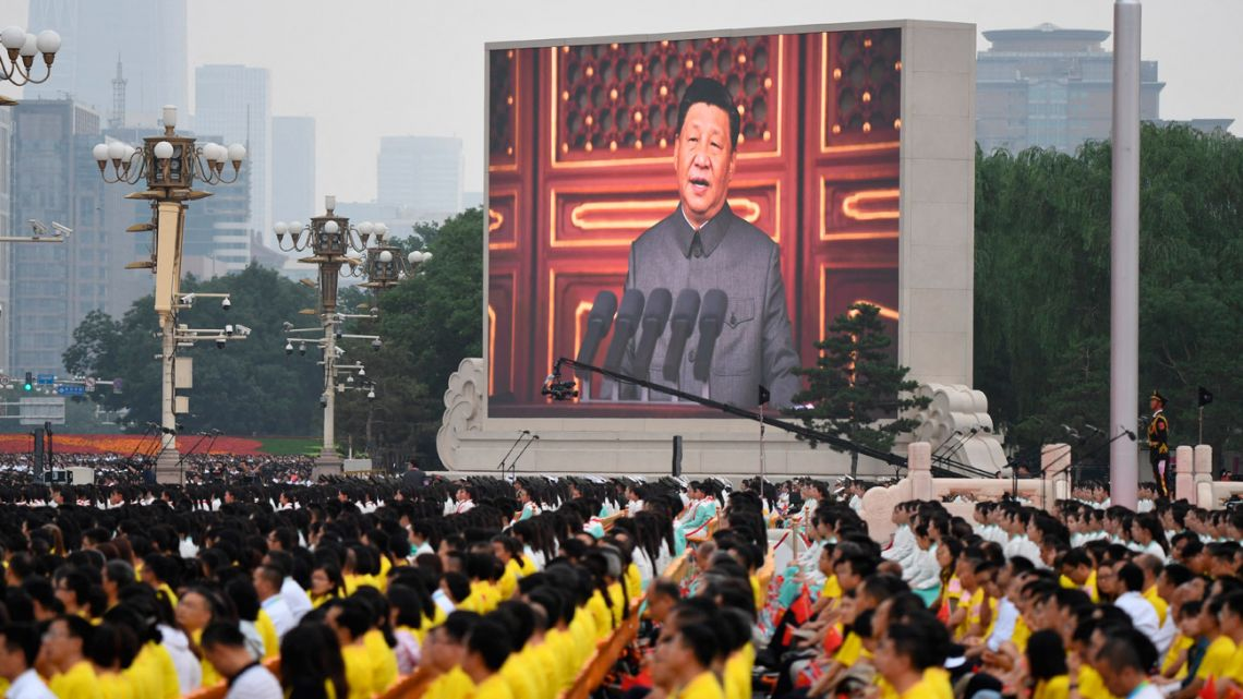 Chinese President Xi Jinping (on screen) delivers a speech during the celebrations of the 100th anniversary of the founding of the Communist Party of China at Tiananmen Square in Beijing on July 1, 2021.