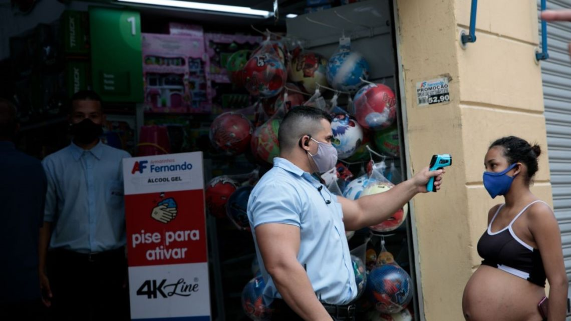 An employee wearing a protective mask takes the temperature of a pregnant shopper waiting to enter a store in São Paulo, Brazil, on Wednesday, June 10, 2020.