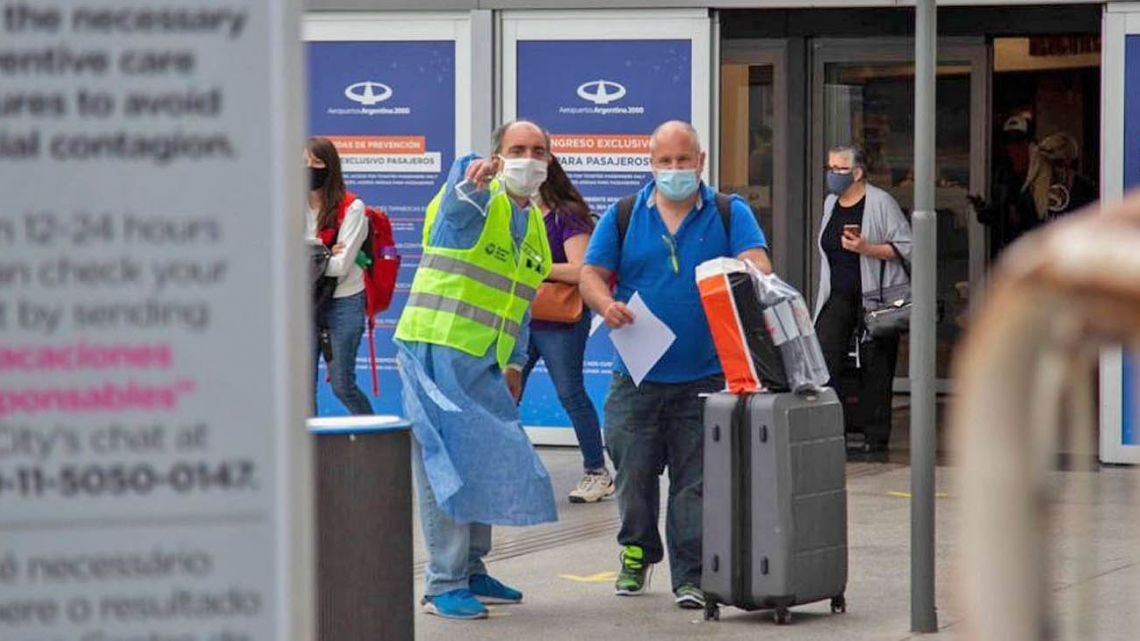 An arriving traveller is directed by a worker at Ezeiza international airport, during the coronavirus pandemic.