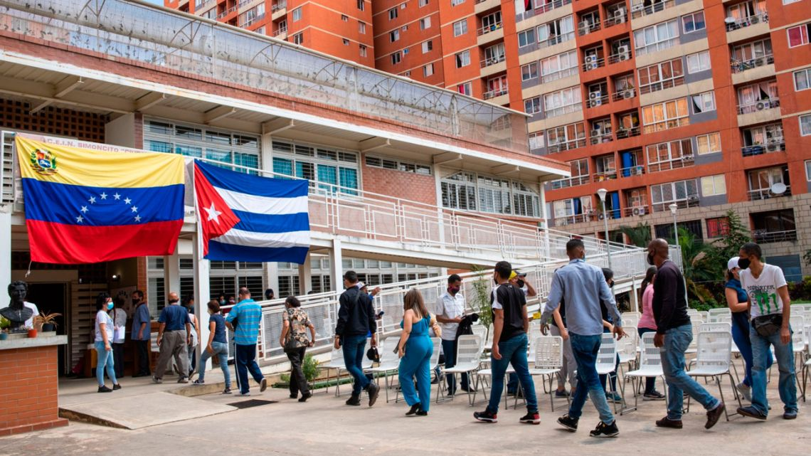 Patients wait in line beneath Venezuelan and Cuban flags to receive the Cuban Abdala Covid-19 vaccine in the Ciudad Tiuna neighbourhood of Caracas, Venezuela, on Thursday, July 1, 2021. Venezuela expects to receive 12 million doses of Abdala, which is said by Cuban authorities to be 92 percent effective.