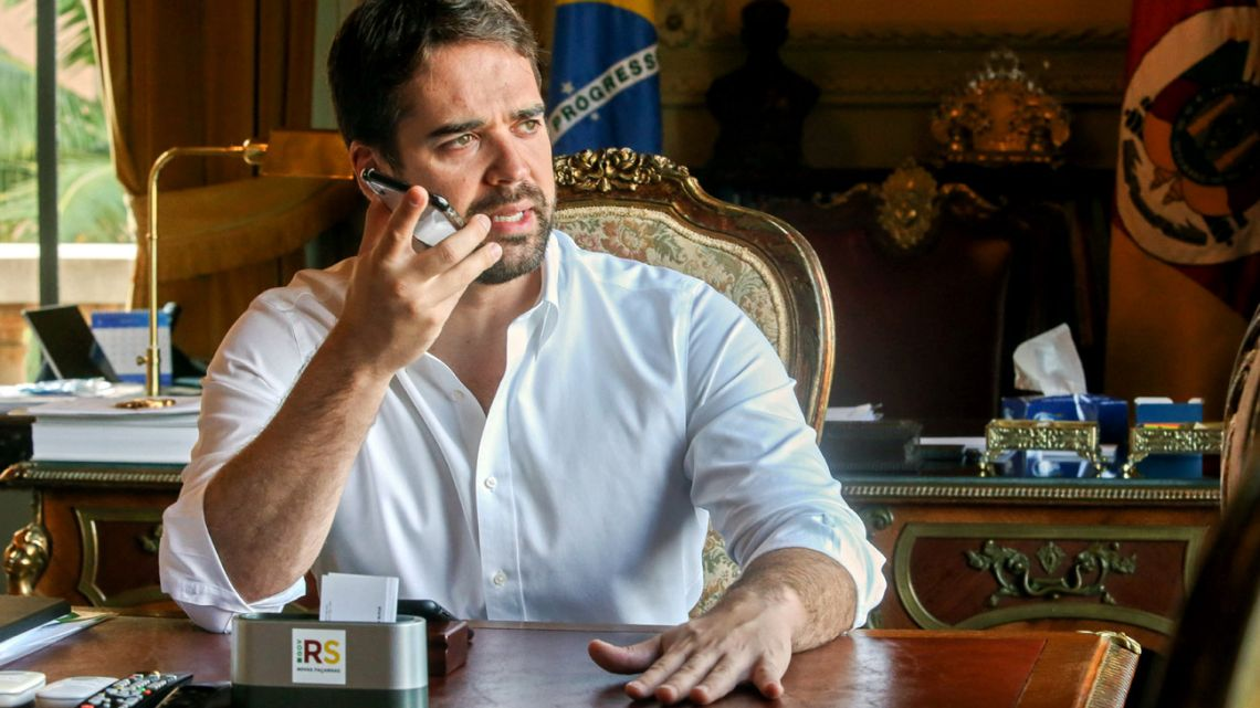 Handout picture released by Agencia Piratini showing Rio Grande do Sul Governor Eduardo Leite talking on a mobile phone at his office of the Piratini Palace in Porto Alegre, Rio Grande do Sul, Brazil, on March 27, 2020.