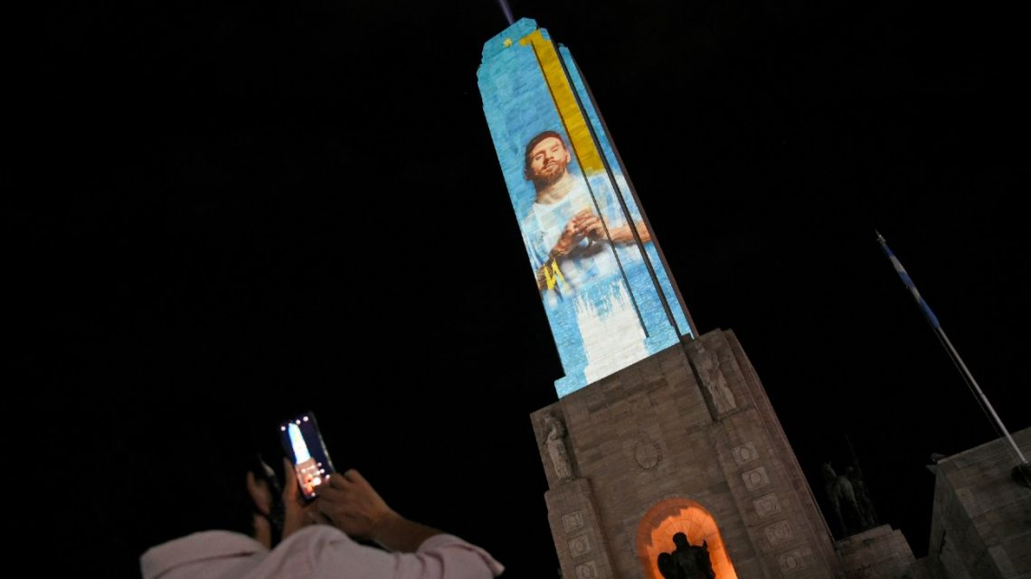 A man takes a picture of a monument in Rosario with an image of football star Lionel Messi's image projected on it, as part of a video mapping show in support of the Argentine national football team, on July 9, 2021.