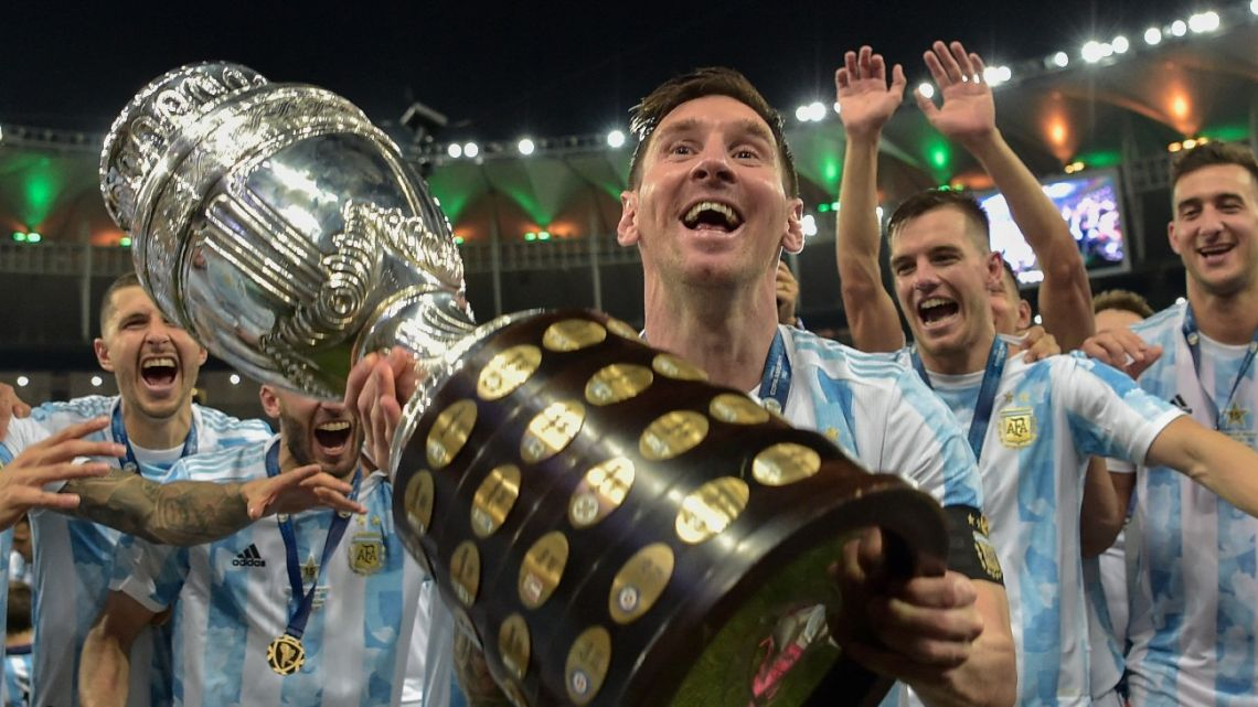 Lionel Messi holds the Copa América trophy as he celebrates with teammates.