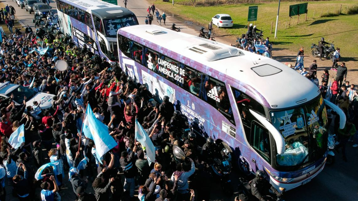 Aerial view of fans surrounding buses transporting Argentina's football team upon its arrival in Ezeiza at AFA headquarters, after winning the 2021 Copa América final match against Brazil.