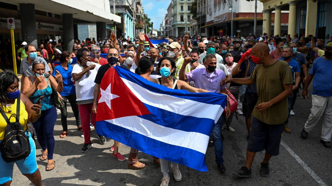 """People take part in a demonstration to support the government of the Cuban President Miguel Díaz-Canel in Havana, on July 11, 2021. Thousands of Cubans took part in rare protests Sunday against the communist government, marching through a town chanting """"Down with the dictatorship"""" and """"We want liberty."""""""