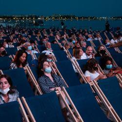 La gente ve una película en el cine al aire libre de Macé Beach (Cinema de la Plage) en la Croisette de Canne al margen de la 74ª edición del Festival de Cine de Cannes en el sur de Francia. | Foto:John Macdougall / AFP
