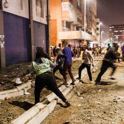 Agentes de los Servicios de Policía de Sudáfrica (SAPS) impiden que los saqueadores realicen sus acciones en el centro de Durban. - Varias tiendas resultan dañadas y se queman coches en Durban, tras una noche de violencia. | Foto:AFP