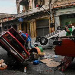 En la foto se ven coches de la policía volcados en la calle en el marco de una manifestación contra el presidente cubano Miguel Díaz-Canel en La Habana. | Foto:Yamil Lage / AFP