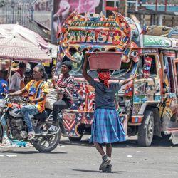 Una mujer cruza una calle muy transitada en Puerto Príncipe tras el asesinato del presidente haitiano Jovenel Moise. | Foto:Valerie Baeriswyl / AFP