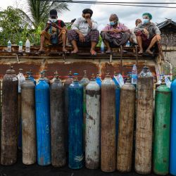 La gente espera para llenar los tanques de oxígeno vacíos fuera de una fábrica en Mandalay, en medio de un aumento de los casos de coronavirus Covid-19. | Foto:STR / AFP
